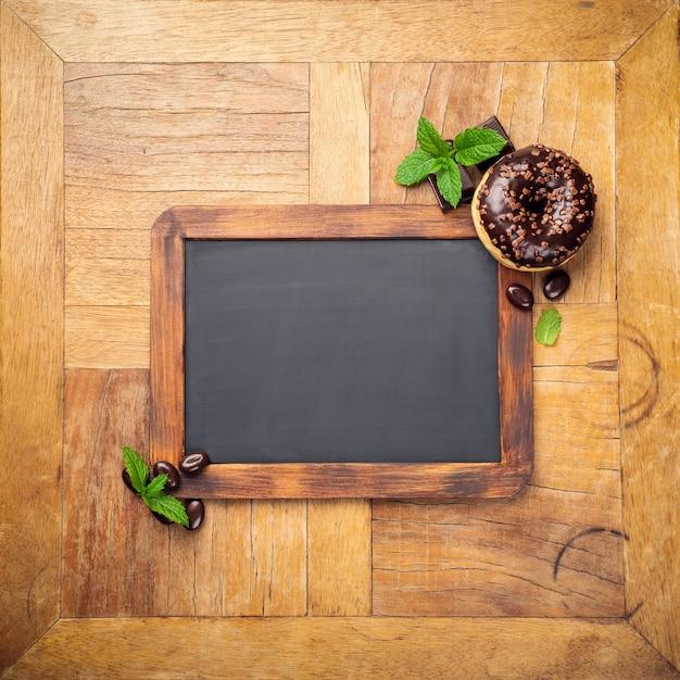 Lavagna nera con ciambella glassata al cioccolato Foto Premium