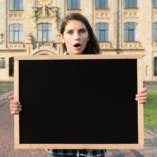 Lavagna sorpresa della tenuta della ragazza della high school del colpo medio Foto Gratuite