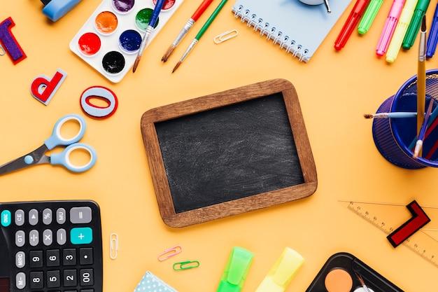 Lavagna vuota circondata da materiale scolastico sparsi sulla scrivania gialla Foto Gratuite