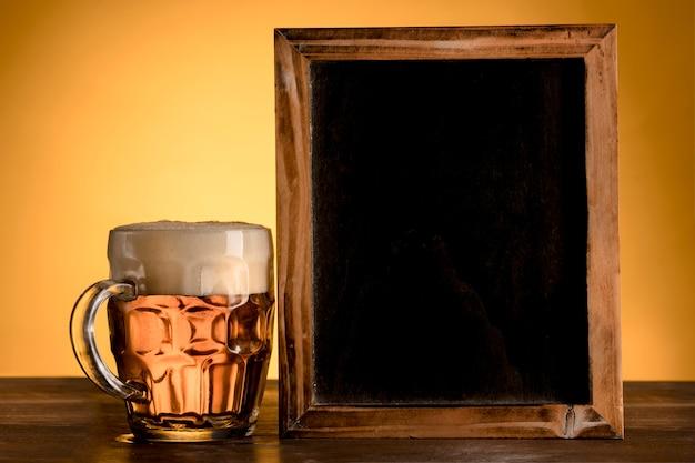 Lavagna vuota con bicchiere di birra sulla tavola di legno Foto Gratuite