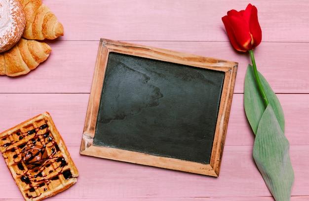 Lavagna vuota con waffle belga e tulipano Foto Gratuite