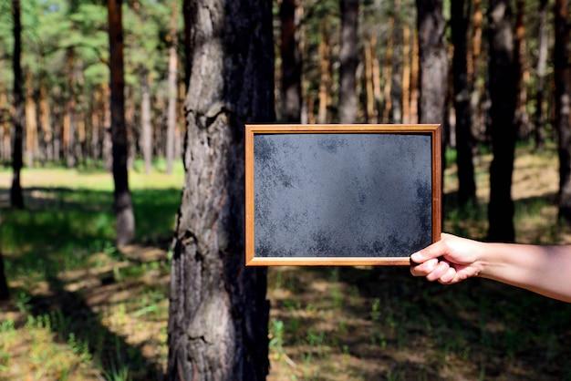 Lavagna vuota nera nella mano destra di un uomo Foto Premium