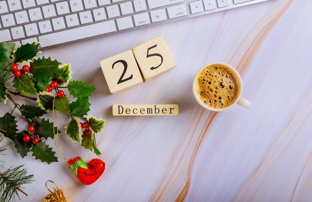 Lavora la scrivania con una composizione di natale tastiera computer tazza di caffè con il 25 dicembre cristmas day Foto Premium