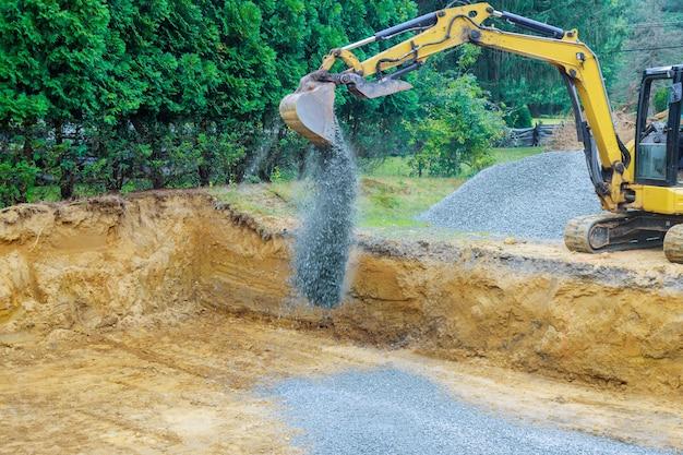 Lavorando su un escavatore edile muovendo pietre di ghiaia per la costruzione di fondamenta Foto Premium