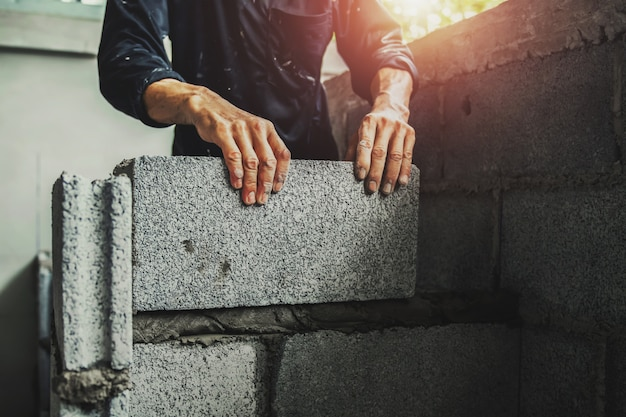 Lavoratore che costruisce mattoni di parete con cemento Foto Premium
