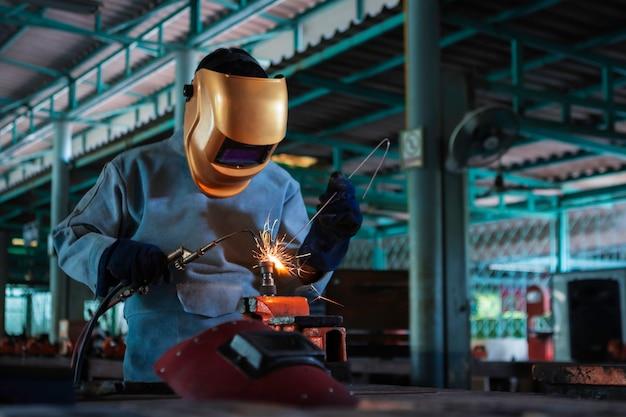 Lavoratore circa l'acciaio del saldatore usando la saldatrice elettrica Foto Premium