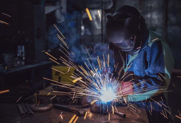 Lavoratore del lavoratore industriale presso la fabbrica di saldatura della struttura in acciaio Foto Premium