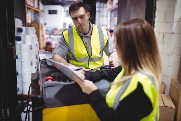 Lavoratore del magazzino che parla con il driver del carrello elevatore in magazzino Foto Premium