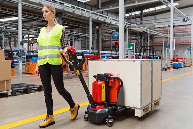 Lavoratore del magazzino che trascina il transpallet manuale o il carrello elevatore manuale con il pallet della spedizione che scarica in un camion Foto Premium