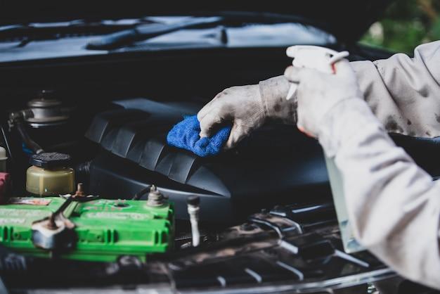 Lavoratore dell'autolavaggio che indossa un'uniforme bianca che sta una spugna per pulire l'automobile nel centro dell'autolavaggio, concetto per industria di cura di automobile. Foto Gratuite