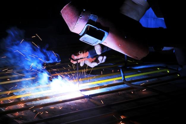 Lavoratore dell'industria che salda struttura d'acciaio in fabbrica, saldatura spa Foto Premium