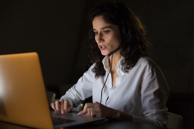 Lavoratore di call center serio con auricolare e laptop Foto Gratuite