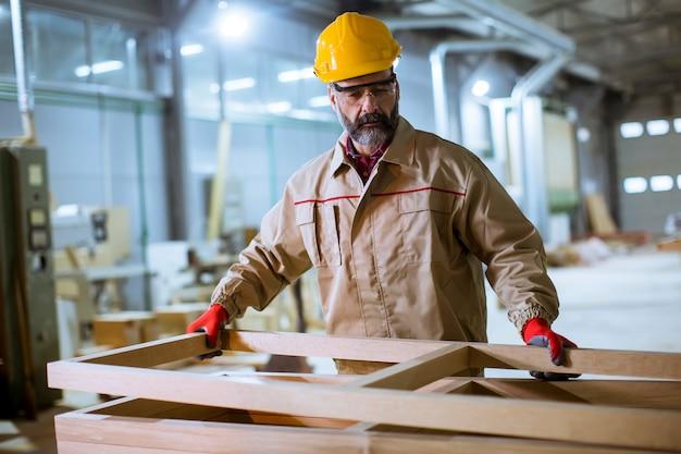 Lavoratore invecchiato centrale bello che lavora nella fabbrica della mobilia Foto Premium