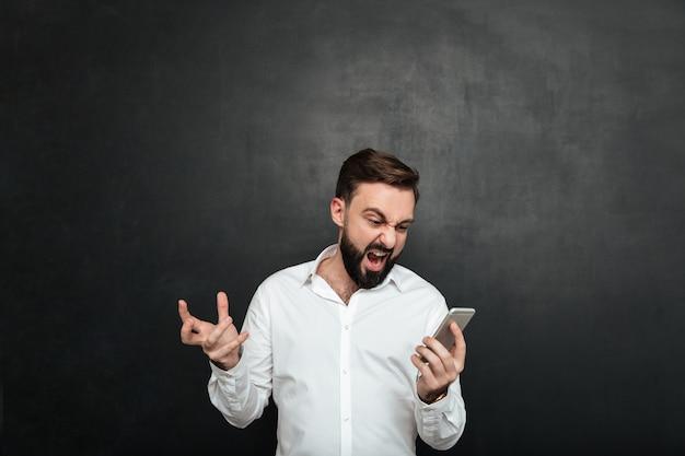 Lavoratore maschio emozionale che grida nella rabbia e nello sdegno mentre osservando sullo schermo dello smartphone d'argento sopra grigio scuro Foto Gratuite