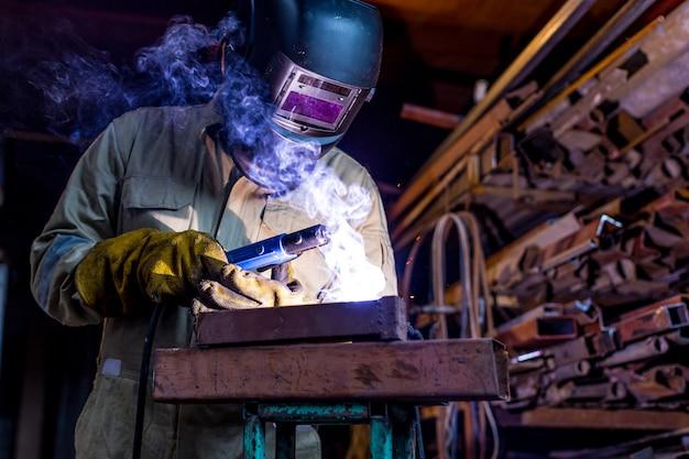 Lavoratore operaio industriale in fabbrica saldando la struttura in acciaio con maschera protettiva e uniforme. Foto Premium