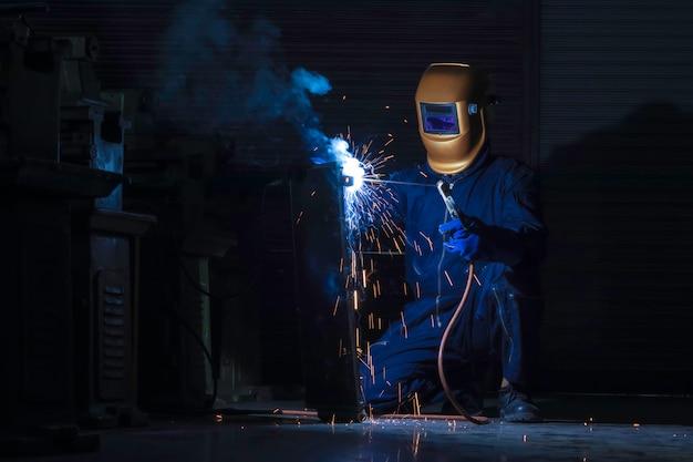 Lavoratore saldatore in acciaio usando la saldatrice elettrica Foto Premium