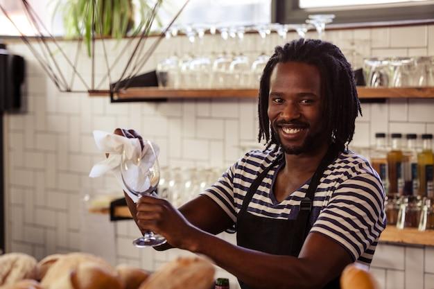 Lavoratore sorridente dei pantaloni a vita bassa che pulisce i vetri Foto Premium