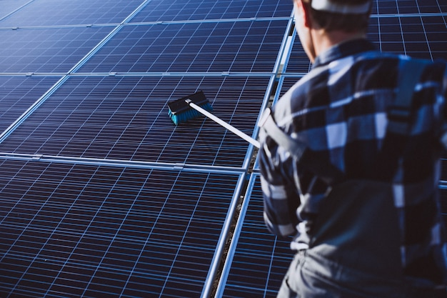 Lavoratore uomo nel firld dai pannelli solari Foto Gratuite