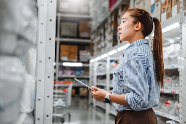 Lavoratrice asiatica che lavora con la compressa digitale che controlla le scatole Foto Premium