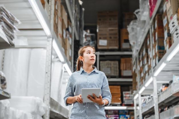 Lavoratrice asiatica che lavora con le caselle di controllo digitali della compressa Foto Premium