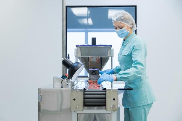 Lavoratrice dell'industria farmaceutica nella produzione operativa di indumenti protettivi di compresse in condizioni di lavoro sterili Foto Premium