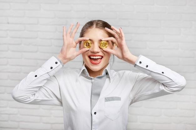 Lavoratrice sorridente in camicetta astuta bianca che mette bitcoins dorati davanti ai suoi occhi Foto Premium