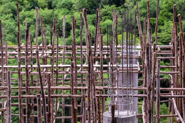 Lavori di costruzione con cemento e legno, colata di colonne di malta cementizia, impalcature e lavori di costruzione, edifici nella foresta Foto Premium