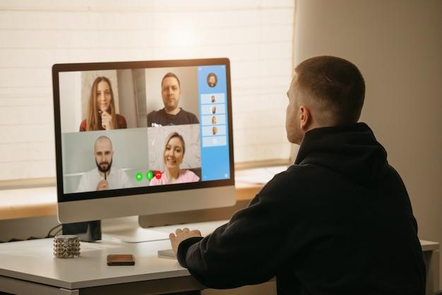 Lavoro a distanza. una vista posteriore di un uomo durante una videochiamata con i suoi colleghi sul computer desktop. un membro di un briefing online che lavora da casa. Foto Premium