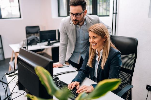 Lavoro di computer di supervisione del capo esecutivo maschio di giovane impiegato femminile. Foto Premium