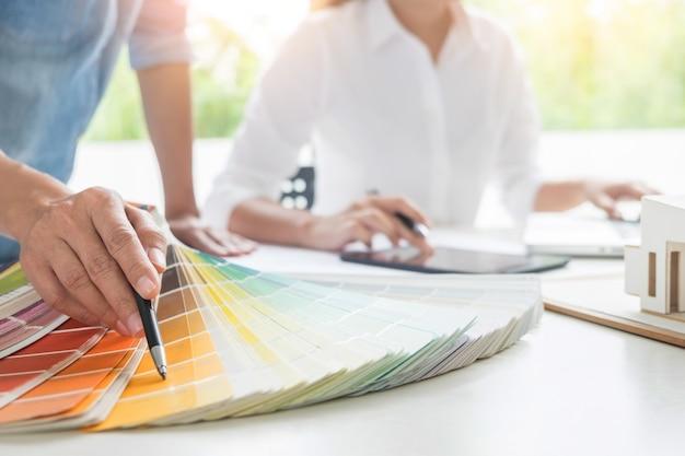 Lavoro di squadra di designer creativi o interni con swatch pantone e piani di costruzione su scrivania, architetti che scelgono campioni di colore per il progetto di progettazione Foto Premium