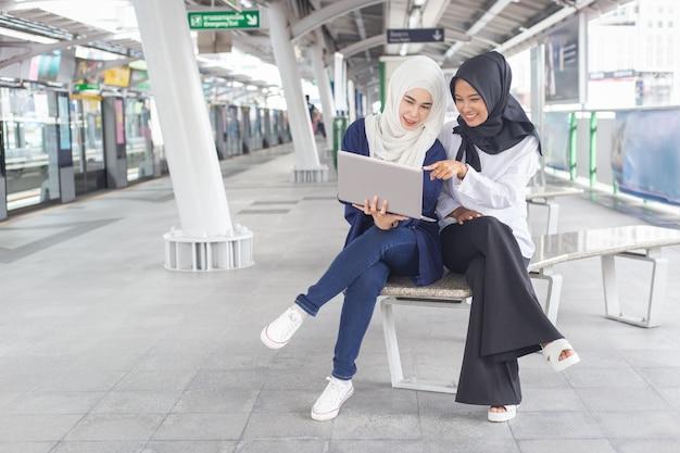 Lavoro per due persone della bella giovane ragazza asiatica ad uno skytrain con un computer portatile. donne musulmane Foto Premium