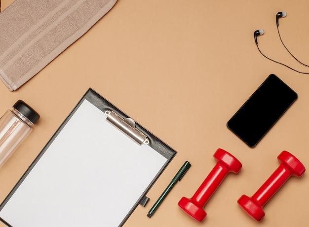 Lay piatto di attrezzature sportive per il fitness su una superficie beige Foto Premium