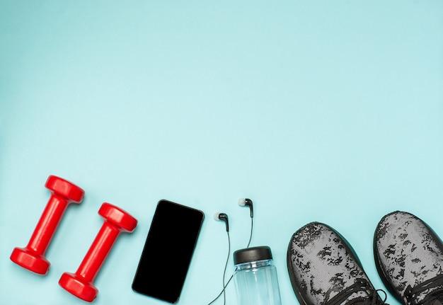 Lay piatto di attrezzature sportive per il fitness su una superficie blu Foto Premium