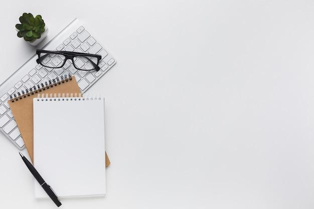 Lay piatto di notebook e occhiali sul desktop Foto Gratuite