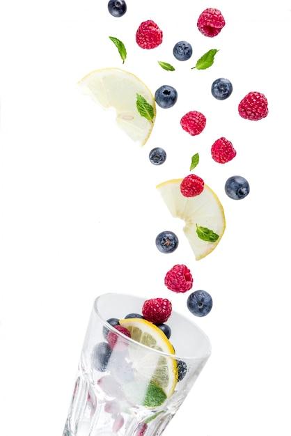 Layout creativo con bacche fresche, modello semplice. lampone, mirtillo, foglie di menta, fettine di limone. concetto di un drink estivo mojito, limonata, con un bicchiere. Foto Premium