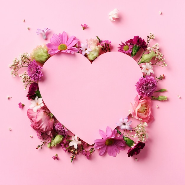 Layout creativo con fiori rosa, cuore di carta su sfondo pastello incisivo. carta di san valentino. cuore cutted in incisivo fondo di carta pastello. Foto Premium