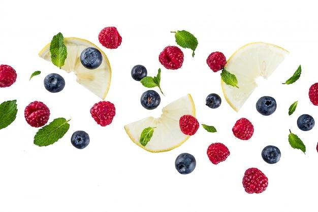 Layout creativo, tavolo, con bacche fresche, modello semplice sul tavolo bianco. lampone, mirtillo, foglie di menta, fettine di limone. Foto Premium