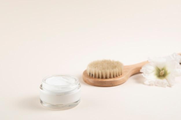 Layout di crema e spazzola per capelli con sfondo semplice Foto Gratuite