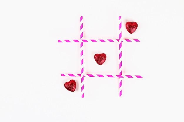 Layout giorno di san valentino. insignificante e croci rosa cannucce e cuori su uno sfondo bianco. tic tac toe. Foto Premium