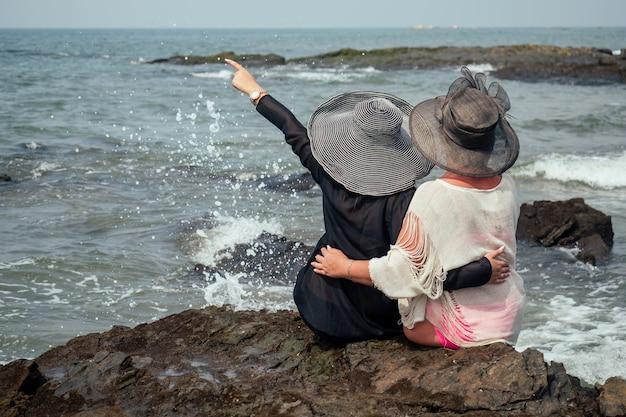 Le amiche allegre sulla spiaggia si siedono in cappelli Foto Premium