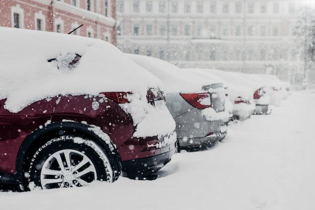 Le auto parcheggiate sono bloccate nella neve dopo una forte tempesta di neve al parcheggio Foto Premium