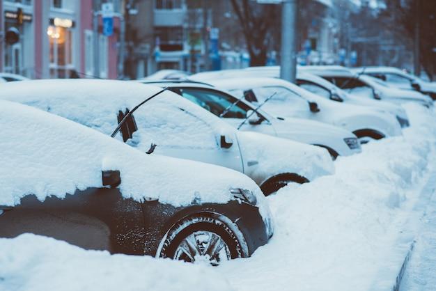 Le auto sono parcheggiate lungo le strade coperte di neve Foto Premium