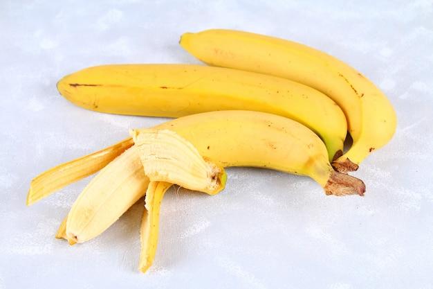Le banane sono intere e tagliate su una fetta in una tazza su uno sfondo grigio Foto Premium