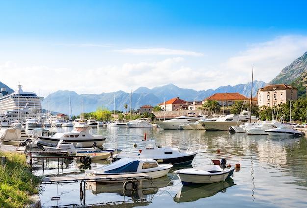 Le barche in mare al tramonto con le montagne e la città vecchia Foto Premium