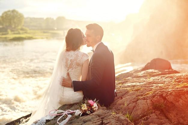 Le belle coppie amano baciare mentre si siedono sulle rocce vicino al fiume Foto Premium