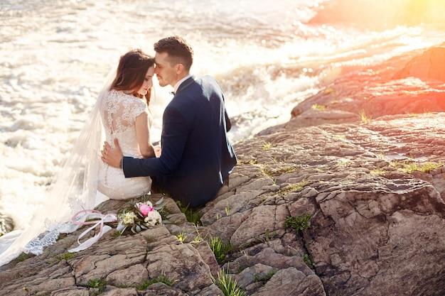 Le belle coppie amano il bacio mentre si siedono sulle rocce Foto Premium