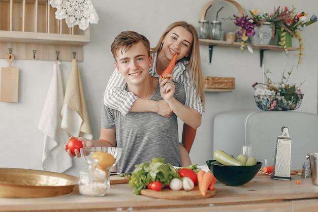 Le belle coppie preparano l'alimento in una cucina Foto Gratuite