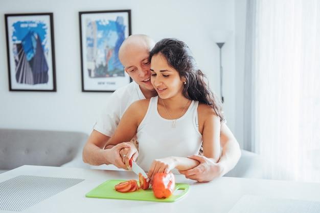 Le belle giovani coppie macinano insieme le verdure nella cucina. Foto Premium