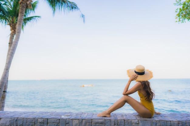 Le belle giovani donne asiatiche del ritratto felici si rilassano il sorriso intorno all'oceano della spiaggia del mare Foto Gratuite
