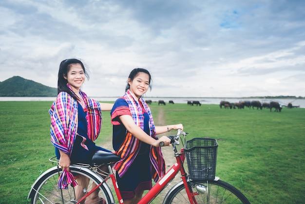 Le belle ragazze asiatiche godono del viaggio alla campagna della tailandia guidando sulla bicicletta Foto Premium